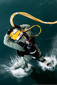 A US Navy surface supplied diver wearing a lightweight demand helmet and holding the umbilical at head level is shown entering the water by jumping in. The view is from the deck from which the diver has jumped, and shows the back of the diver as the fins first contact the water