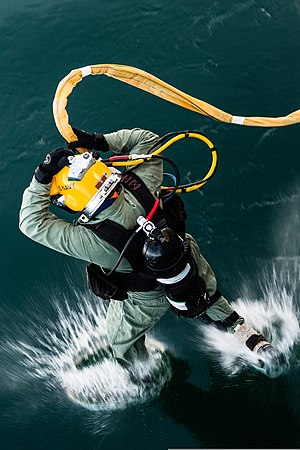 A Navy salvage diver leaps feet first into calm dark green seawater.