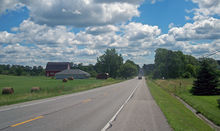 A road under a blue sky with white clouds goes past a farm on the left with rolls of hay in its fields and a red barn. In the distance the road climbs a small rise