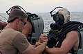 US Navy 031014-N-2420K-004 Information Systems Technician 2nd Class Matthew Grove prepares to lower (EOD) dive officer, Lt. Ryan Bedner, into Sasebo Bay.jpg