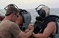 US Navy 031014-N-2420K-004 Information Systems Technician 2nd Class Matthew Grove prepares to lower (EOD) dive officer, Lt. Ryan Bedner, into Sasebo Bay.jpg
