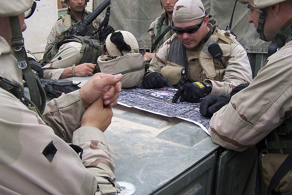 US Navy 041116-N-1438S-004 Chief Engineering Aide Ardell Ball, center, assigned to Naval Mobile Construction battalion Four (NMCB-4), studies an aerial photograph of the streets in Fallujah, Iraq