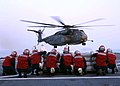 US Navy 050903-N-8002S-125 U.S. Navy flight deck personnel take cover from the rotor wash as an MH-53E Sea Dragon helicopter takes off from the dock landing ship USS Tortuga (LSD 46).jpg