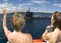 US Navy 060525-N-9662L-128 Two spouses wave to their husbands aboard the fast attack submarine USS City of Corpus Christi (SSN 705) during their return to Apra Harbor after a routine underway.jpg