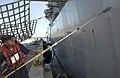 US Navy 060904-N-9851B-006 Fire Controlman 3rd Class Vernon McDaniel, assigned to the guided missile destroyer USS Hopper (DDG 70), paints the side of the ship during a port visit to Guam.jpg