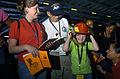 US Navy 070822-N-3038W-181 Damage Controlman 3rd Class Felicity Prestianni, right, from engineering department's damage control division, helps a young Tiger try on a firefighting helmet that is part of a fire fighting ensemble.jpg
