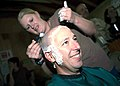 US Navy 071031-N-0321S-407 Utilitiesman Constructionman Amanda Lenhart, a Seabee assigned to Naval Mobile Construction Battalion (NMCB) 15, shaves the head of Senior Chief Steelworker Gregory Davison.jpg