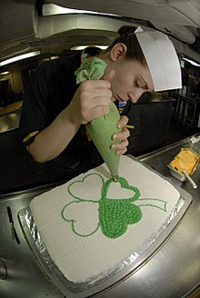 US Navy 090317-N-2475A-043 Culinary Specialist 3rd Class Rechele Rosposa, from Bremerton, Wash., decorates a Saint Patrick's Day cake in the ship's bake shop aboard the aircraft carrier USS John C. Stennis (CVN 74).jpg