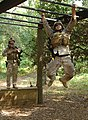 US Navy 100712-N-8968M-380 Explosive Ordnance Disposal technician 2nd Class Justin Eaton speeds across the monkey bars while going through an obstacle course during a training exercise.jpg