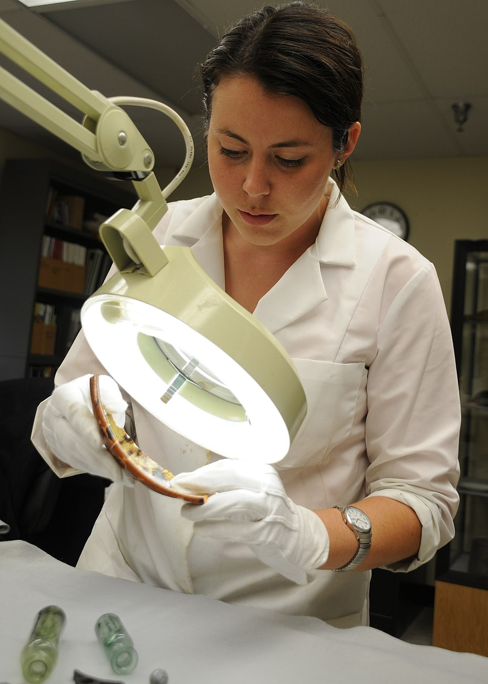 US Navy 100803-N-9671T-004 Kate Morrand, an artifact conservator at Naval History and Heritage Command, inspects a piece of pottery recovered from the wreck of the sloop-of-war USS Scorpion