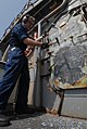 US Navy 110720-N-DU438-229 Fire Controlman 2nd Class Justin Heisterkamp chips paint from a hatch during preservation aboard the guided-missile crui.jpg