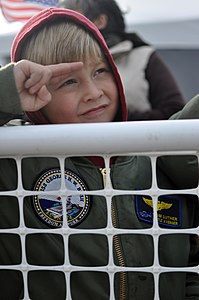 US Navy 111210-N-FU443-672 A Sailors son salutes the ship as it pulls into Naval Station Norfolk.jpg