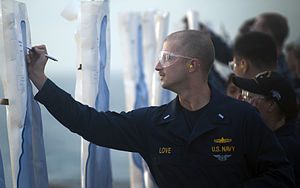 US Navy 111210-N-PB383-302 Lt. j.g. Patrick Love writes his name on a target during small arms qualifications aboard the amphibious transport dock.jpg
