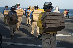 US Navy 120129-N-KS651-181 Sailors aboard the amphibious dock landing ship USS Pearl Harbor (LSD 52) carry supplies from the flight deck during a r.jpg