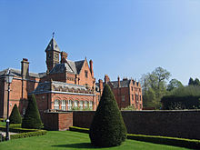 An irregularly shaped red-brick house with slate roofs with an orangery on the ground floor and gables, chimneys and a clock tower above. In the foreground is a formal garden with a lawn, clipped shrubs, a wall and a Victorian-style lamppost.