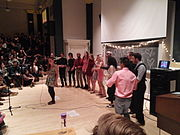 A row of singers dressed mostly in pink and black support a soloist holding a microphone in front of a full house in a small, darkened, crowded auditorium.