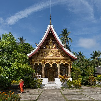 Vat Pa Phai temple with a Buddhist monk, orange marigold, clouds and blue sky, in Luang Prabang.jpg