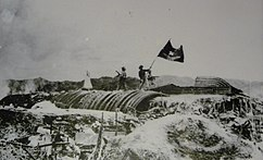 Viet Minh wave their flag over a captured French bunker at Dien Bien Phu in 1954. The French defeat at the Battle of Ðiện Biên Phủ led to the Geneva Conference and the partition of Vietnam into north and south.
