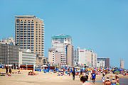 High-rise hotels line the ocean front covered with colorful beach-goers.