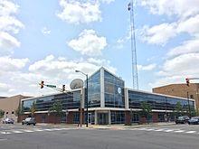 WNIT Center for Public Media en el centro de South Bend.  El edificio está hecho principalmente de vidrio y tiene una pantalla grande que muestra la transmisión en vivo del canal de televisión pública de WNIT.
