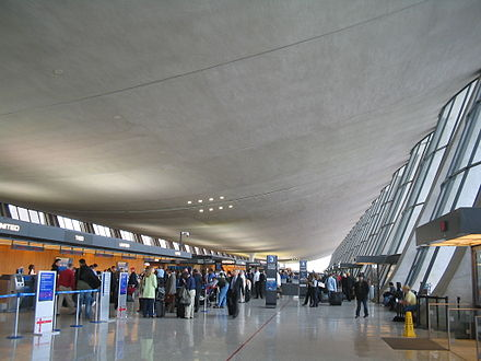 The terminal ceiling is suspended in a catenary curve above the luggage check-in area. - Washington Dulles International Airport