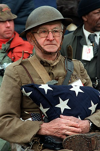 Veterans Day - U.S. World War I veteran Joseph Ambrose (1896–1988) attends the dedication parade for the Vietnam Veterans Memorial holding the flag that covered the casket of his son, who was killed in the Korean War.