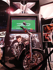 A silver motorcycle with black tires sits on a podium. A TV screen with a green preview displayed sits behind the motorcycle with a large X above it and a picture of Wolverine below