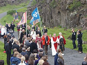 A crowd of people walking along an outdoor path. They are led by individuals in robes and a number carry flag banners.
