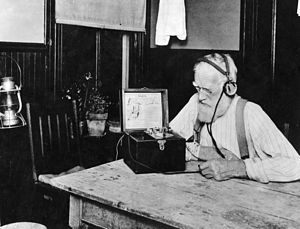 "AM broadcasting - Farmer listening to U.S. government weather and crop reports using a crystal radio. Public service government time, weather, and farm broadcasts were the first radio ""broadcasts""."