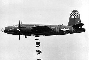 Bombsight - The way the line of bombs falling from this B-26 goes toward the rear is due to drag. The aircraft's engines keep it moving forward at a constant speed, while the bombs slow down. From the bomber's perspective, the bombs trail behind the aircraft.