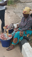 A Nigerian woman packaging and selling groundnuts.png