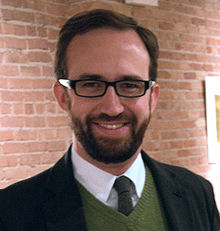 Young, smiling, bearded man with horn-rimmed glasses