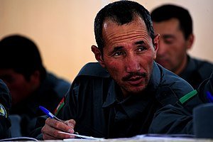 Afghan National Police trainee Nazem Hosain takes notes during a radio communications lesson at Regional Training Center, Bamyan.jpg
