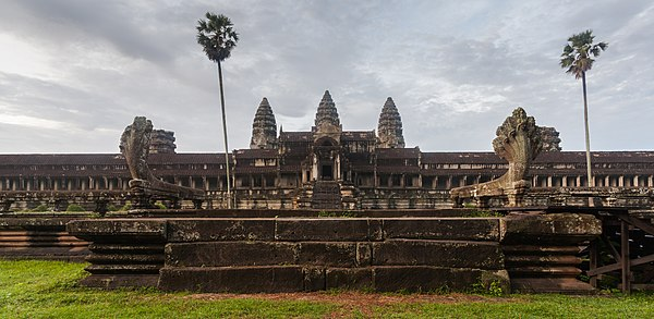Dawn view of the temple of Angkor Wat, with 2 Nāgas in the foreground, a gallery in the middle and the temple mountain in the back. The Angkor Wat was first a Hindu and later a Buddhist temple complex built by the Khmer King Suryavarman II in the early 12th century, and capital of the Khmer Empire, today Cambodia. This temple complex is the best preserved temple in the site and a symbol of Cambodia, appearing on its national flag.
