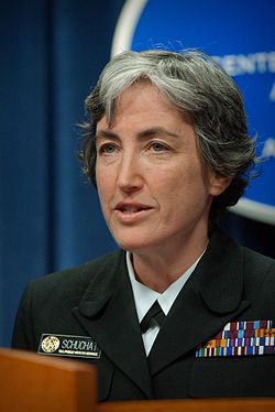 A woman with silver-colored hair in a military uniform looking left with her mouth slightly agape