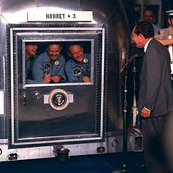 Photo of the three crew members smiling at the President through the glass window of their quarantine chamber. President Nixon is standing at a microphone, also smiling.