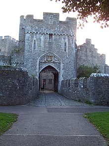 the gateway to the castle through a tower with portcullis