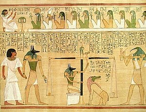 "Anubis - The ""weighing of the heart,"" from the book of the dead of Hunefer. Anubis is portrayed as both guiding the deceased forward and manipulating the scales, under the scrutiny of the ibis-headed Thoth."