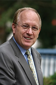 A bespectacled Barry Stuppler in a tan suit, blue shirt, and gold tie.