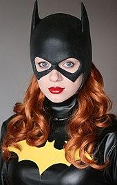 Photographie couleur du buste d'une jeune femme déguisée en Batgirl.