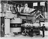 Schwarzweißbild einer schweren Maschine mit zwei beiseite sitzenden Bedienern