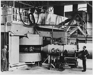Cyclotron - Lawrence's 60-inch cyclotron, with magnet poles 60 inches (5 feet, 1.5 meters) in diameter, at the University of California Lawrence Radiation Laboratory, Berkeley, in August, 1939, the most powerful accelerator in the world at the time. Glenn T. Seaborg and Edwin M. McMillan (right) used it to discover plutonium, neptunium, and many other transuranic elements and isotopes, for which they received the 1951 Nobel Prize in chemistry. The cyclotron's huge magnet is at left, with the flat accelerating chamber between its poles in the center. The beamline which analyzed the particles is at right.
