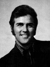 A dark-haired man wearing a shirt and a dark jacket, smiling broadly