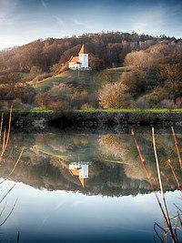 Blick über das Wasser der Alt-Donau auf die Kirche St. Felizitas.jpg