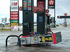 A gas pump laying on its side. The sign for the gas station is visible in the background.