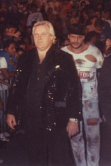 Bobby Heenan, dressed in a black sequin jacket, leads The Brooklyn Brawler to the ring in the late 1980s