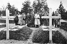 17 hombres, la mayoría con uniforme militar, se encuentran en un cementerio, inspeccionando dos tumbas.