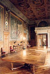 Grande table de réception au centre avec des tapisseries aux murs et un plafond à caissons