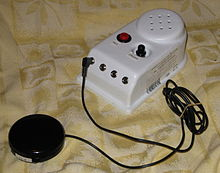 a small electronic device with several buttons, there is a cable going from the device to an activation button.