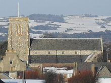 Side view of the upper section and tower of a long, flint-built church with snow-covered hills in the background and various rooftops in the foreground. A tall tower rises on the left.